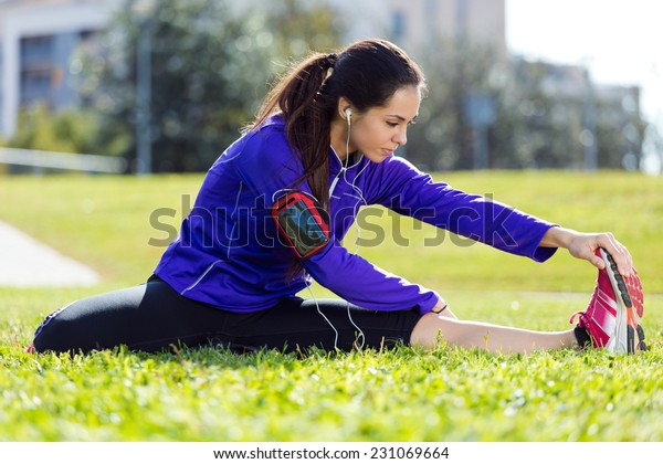 Outdoor portrait of young woman stretching and preparing for running.