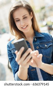 Outdoor portrait of young woman using mobilephone, smiling.