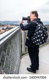 Outdoor profile view of a Caucasian male photographer in black suit and backpack at a tower with digital camera taking pictures of city view.