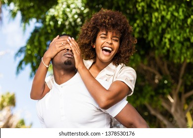 Outdoor protrait of black african american couple - Guy carrying girfriend on his back