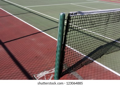 An outdoor public tennis court with sunshine