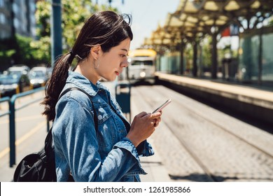 outdoor railway station commute woman after work waiting for metro to arrive on platform in san francisco. young female people on public transport platform using mobile phone texting replying emails.