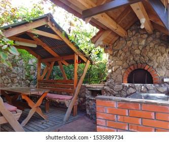 Outdoor recreation area with barbecue, brazier, gazebo, table and bench under a canopy of refractory bricks, natural stone and wood.