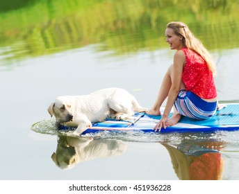 Outdoor recreation. The beautiful girl and a dog in the boat. Dog of breed Labrador.