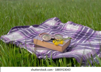Outdoor recreation. The book is lying on a blanket in the green grass in the light of the sun. Picnic in the field. A blanket with things lies in the grass on a bright day. A book, glasses, a blanket