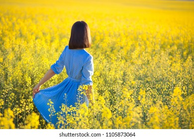 Outdoor recreation concept. Girl in blue dress looking ahead on yellow blooming field. Girl without allergy enjoying beautiful meadow in bloom.