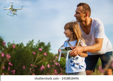 outdoor recreation Leisure for family. Birthday gift. A man and little girl launch a radio-controlled aircraft or a drone or a helicopter into the sky.