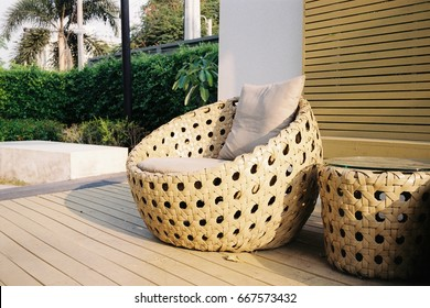Outdoor relaxing space with trees around and rattan sofa in close up view