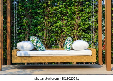 An outdoor resin wicker porch swing with white cushion and leaves pattern pillows in the garden with nature background.