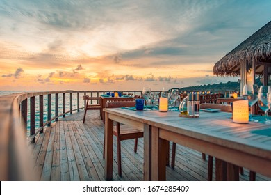 Outdoor restaurant at the beach. Table setting at tropical beach restaurant. Led light candles and wooden tables, chairs under beautiful sunset sky. Luxury hotel or resort restaurant
