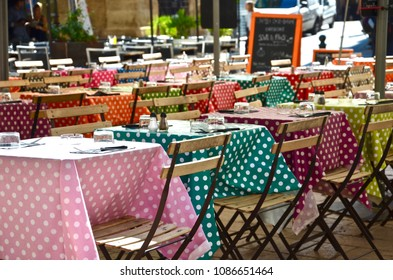 Outdoor restaurant with colorful dot design settings and wooden chairs in Aix-en-Provence in South France