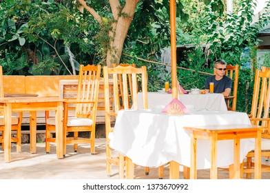 Outdoor restaurant with man sitting on table - Cirali, Antalya Province, Turkey, Asia
