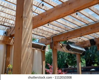 An outdoor restaurant set up with patio and wooden overhang and speakers