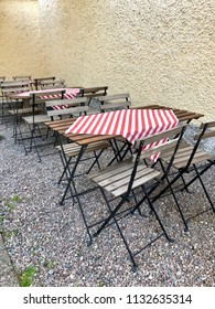 Outdoor restaurant tables and chairs in a row with red and white table cloth, against a yellow plastered wall with gravel ground on backyard.