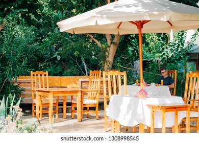 Outdoor restaurant with umbrella and man sitting on table - Cirali, Antalya Province, Turkey, Asia