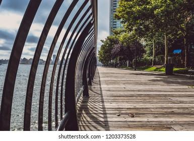 Outdoor riverfront walkway. Wooden outdoor pavilion walkway running path. Black steel railing. Modern New York City Skyline background. Light and shadow on wooden plank floor.