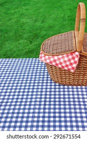 Outdoor Rustic Picnic Table  With Hamper And Blue Checkered Tablecloth On The Lawn In The Park Rest Area. Breaking Concept