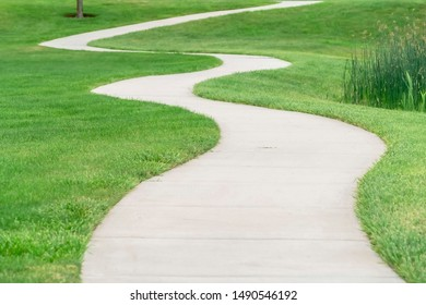 Outdoor scenery with a pathway winding through a terrain covered with grasses
