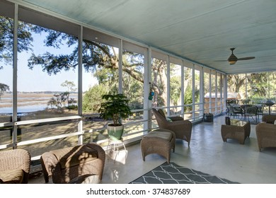 Outdoor screen porch with waterfront view and furniture
