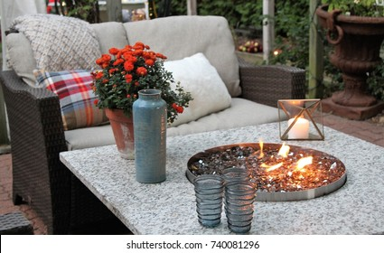 Outdoor seating arrangement around a gas fire pit table in the fall