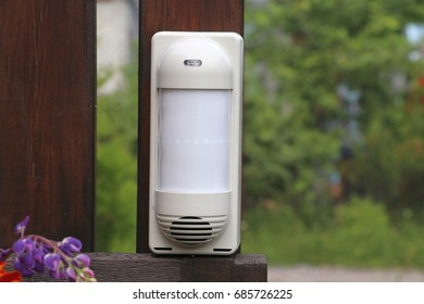 Outdoor security system infrared detector on the wooden post