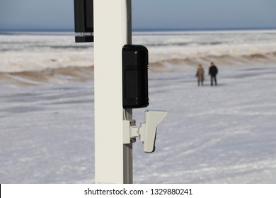 Outdoor security system sensors on the wooden post. Beam and PIR detectors