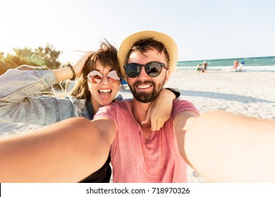 Outdoor self portrait of  young  traveling couple in love , best friends , having fun on  amazing tropical beach.   Attractive wonder girl with  stylish hipster boyfriend enjoying holidays.