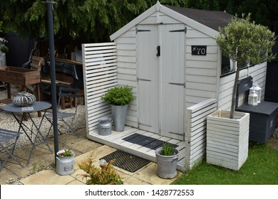 An outdoor she shed used for crafts and sewing in a British garden.