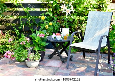 Outdoor sheltered brick patio setting with deck chairs for relaxing afternoons or summer al fresco dining in beautifully landscaped backyard garden