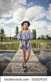 Outdoor shoot of young beautiful, fashionable, playful, chic, woman posing on a small bridge