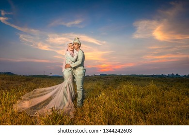 Outdoor shooting for Malay wedding, the bride and groom wearing Malay traditional cloth with  beautiful sunset   as background .