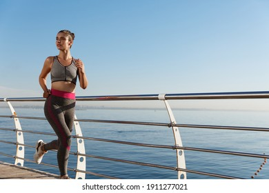 Outdoor shot of attractive fitness woman in sport clothing, jogging and training near sea