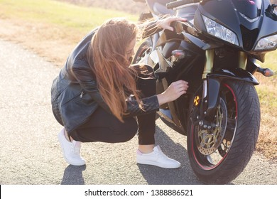 Outdoor shot of attractive woman with long dark hair squating near her modern motobike, wearing black clothes and white sneakers, trying to fix broken motobike. Travelling, adrenaline concept.