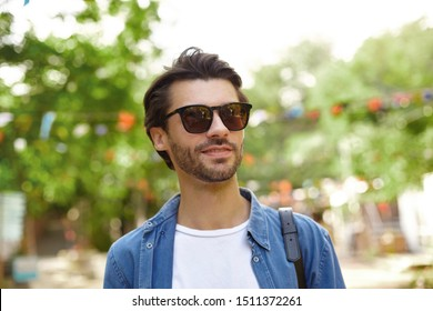 Outdoor shot of beautiful bearded young man in sunglasses posing over city garden on warm sunny day, wearing blue shirt and white t-shirt