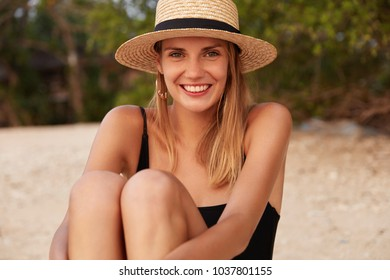 Outdoor shot of beautiful female wears straw hat and swimsuit, sits on hot sandy beach, being satisfied with weather conditions and good rest, feels happy and relaxed. Woman on sandy beach alone