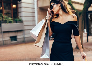 Outdoor shot of beautiful woman with many shopping bags. Asian female model walking on the city street with shopping bags.