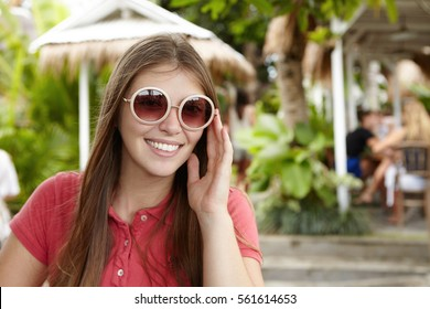 Outdoor shot of beautiful young woman adjusting her hipster round sunglasses and looking at camera with happy facial expression, smiling cheerfully while enjoying long-awaited vacations in hot country