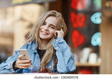 Outdoor shot of carefree attractive and fashionable fair-haired female student in denim jacket, leaning head on hand, browsing in internet via smartphone, standing near asian street food area