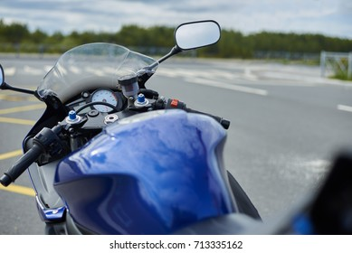 Outdoor shot of clean blue motorbike in empty parking lot with sky and forest in background. Highly-detailed view of vintage custom motorcycle parked outdoors. Subculture and extreme lifestyle