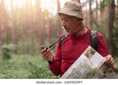 Outdoor shot of eldery man taking part in orienteering trail competitions, being participants of contest, tries to find way, using map and compass. Traveling, adventure and backpacking concept.