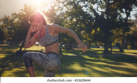 Outdoor shot of fit young woman doing warming up exercises at the park on a sunny day. Female athlete stretching her body before a workout.