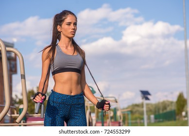 Outdoor shot of focused young woman with jump rope outdoors in nature. Fitness female exercising with jump rope in a park on a sunny day.
