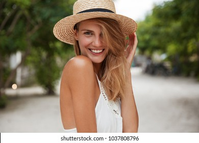 Outdoor shot of good looking young happy female with broad shining smile, wears summer stylish clothing, strols at street across park alone, poses at camera outdoor, satisfied with good rest