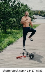 Outdoor shot of handsome fit muscular bearded man does high knee tap exercise, warms up before running, has cardio training, uses sport equipment, has strong body, demonstrates determination