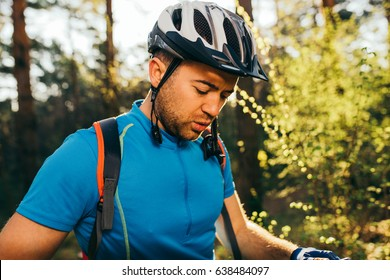 Outdoor shot of handsome young professional mountain biker in helmet and blue cycling t-shirt, standing outdoors in woods, getting ready for cycling contest.