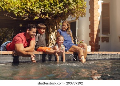 Outdoor shot of happy young family splashing water with hands and legs while sitting on edge of swimming pool. Family enjoying a hot sunny day playing by the pool.