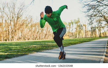 Outdoor shot of a jogger young man running on a trail. Athletic male jogging in the park in the morning in a sunny day. People, healthy lifestyle and sport concept