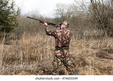 Outdoor shot of man aiming a shotgun.