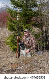 Outdoor shot of man with gun and Russian hunting Spaniel.