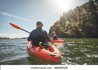 Outdoor shot of mature man canoeing in the lake with woman in background. Couple kayaking in the lake on a sunny day.